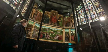 ?? Photos by VIRGINIA MAYO   Associated Press ?? A man views the panels of the Ghent Altarpiece, by Flemish painter Jan Van Eyck, at Saint Bavo Cathedral in Ghent, Belgium, last month. A panel of the masterpiece was stolen in 1934.