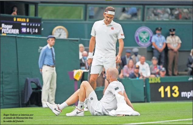 ??  ?? Roger Federer se interesa por el estado de Mannarino tras la caída del francés.