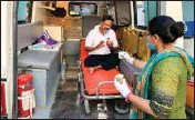 ?? PIC/PTI ?? A volunteer offers water to a COVID-19 patient waiting inside an ambulance, in Ahmedabad, on Wednesday