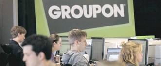 ?? GETTY IMAGES/FILES ?? Employees work on projects at Groupon's international headquarters in Chicago in 2011. U.S. cable provider Comcast Cable recently made a US$250-million investment in the online marketplace.