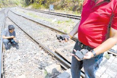 ??  ?? Zoologist Hycintha Aguiar (left) and environmental activist Julio Aguiar collect pieces of coal fallen onto railway tracks from a cargo train at the Kulem railway station in Goa.