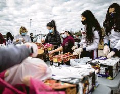 ??  ?? Texans cheerleaders and other volunteers pack food to distribute to hundreds of people picking up supplies Sunday after the freeze.
