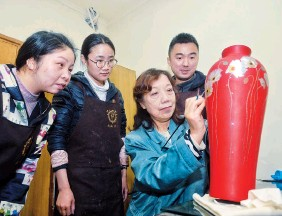 ??  ?? Yin demonstrates to her apprentices how to color lacquerware.
