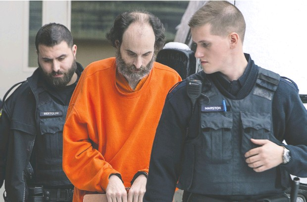 ?? Andrew Vaughan / THE CANADIAN PRESS files ?? Matthew Vincent Raymond, pictured being escorted from a Fredericto­n courthouse last year, is being tried for first- degree murder in the August