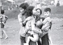 ?? HORST FAAS/ASSOCIATED PRESS ?? Civilians huddle together after an attack by South Vietnamese forces in Dong Xoai in June 1965.