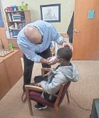 ?? LEFT, PROVIDED BY LEWIS SPEAKS SR.; RIGHT BY JASON SMITH ?? Principal Jason Smith cuts a student's hair. Right, Smith cuts a teammate's hair at Campbell University.