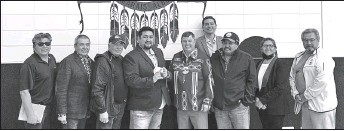 ??  ?? Minister Wilson meets with Chief Silas Yellowknee, member of council Ken Alook and other members of Bigstone Cree Nation. Chief Yellowknee stands second to the left, while member of council Alook and Minister Wilson 'cut' an AITE card in the middle of the group.