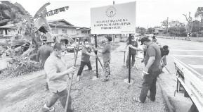 ??  ?? KERJASAMA: Exco dan ahli JKKK Kampung Masjid Jepak bergotong-royong memasang papan tanda di tepi jalan Kampung Masjid Jepak semalam.