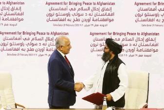 ?? Hussein Sayed / Associated Press 2020 ?? Mullah Abdul Ghani Baradar (right) greets U.S. peace envoy Zalmay Khalilzad at peace talks in Doha, Qatar. Baradar is considered to be the leader of the Taliban's more pragmatic faction.
