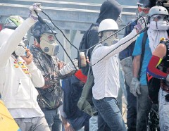 ?? REUTERS ?? Opposition supporters use a giant sling shot to throw a 'Poopootov', a bottle filled with faeces, during a rally against President Nicolas Maduro in Caracas on Wednesday.