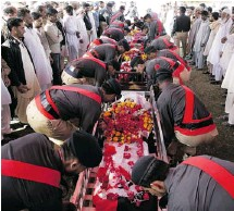 ?? FA­REED KHAN/THE AS­SO­CI­ATED PRESS ?? Pak­istani po­lice of­fi­cers carry coffins Wed­nes­day with the bod­ies of col­leagues killed in Karachi strife. Gun­men wounded a prom­i­nent Sunni cleric and killed his five guards and his driver in the city Tues­day.