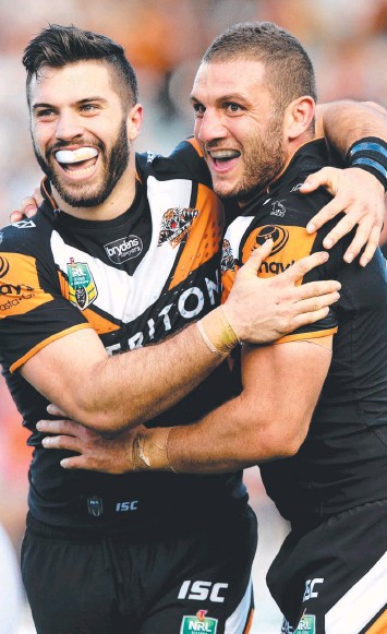 ??  ?? BIG GAMBLE: Tigers James Tedesco (left) and Robbie Farah celebrate a try against the hapless Warriors. Tedesco smashed his way through the team. Picture: Gregg Porteous