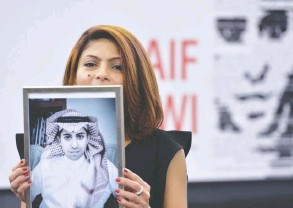 ?? PATRICK HERTZOG / AFP /GETTY IMAGES FILES ?? Ensaf Haidar holds a picture of her husband, Saudi blogger Raif Badawi, jailed since 2012. The Saudis have launched a new investigation against Badawi and Haidar.