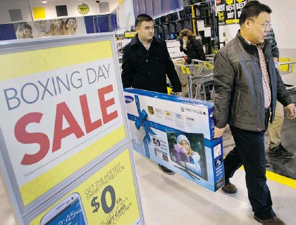 ?? WAYNE CUDDINGTON/OTTAWA CITIZEN ?? Wei Mi and his son Simon, left, found themselves a bargain on a new big-screen television on Boxing Day at Best Buy on Merivale Road.