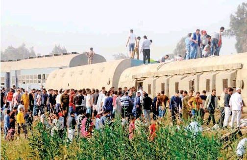 ?? Associated Press ?? ↑ People gather at the site of a train accident near Banha, Qalyubia province, Egypt, on Sunday. At least eight bogies derailed leaving several people dead and over a hundred injured.