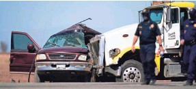 ?? GREGORY BULL/AP ?? Law enforcement officers work at the scene of a deadly crash in Holtville, Calif., on Tuesday where a semitruck crashed into an SUV.