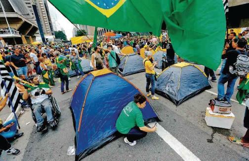 ??  ?? Manifestantes montam acampamento na avenida Paulista, em frente ao prédio da Fiesp; grupo mantém a avenida bloqueada desde a noite de quarta-feira, quando foi divulgado grampo telefônico que revelou que Dilma tentou impedir a prisão de Lula