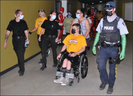 ?? Photos by Matthew Liebenberg/Prairie Post ?? First responders complete a lap of the upper level of the Innovation Credit Union iPlex, Aug. 31. SaskAbilities clients and community members also participated in this Walk, Wheel, Run event.