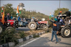 ?? The Associated Press ?? Protesting farmers drive their tractors over road dividers as they march to the capital breaking police barricades during India's Republic Day celebrations in New Delhi, India, Tuesday.