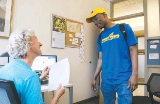 ?? MARVIN JOSEPH/THE WASHINGTON POST ?? Donte Small turns in his final exam Tuesday to professor Jill Zimmerman at Goucher College. Small served a little more than six years in prison at the Maryland Correctional Institution in Jessup, top, where he began taking courses toward the bachelor's...