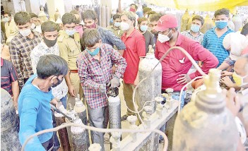 ??  ?? People refill medical oxygen cylinders for Covid-19 coronavirus patients at an oxigen refile station in Allahabad.