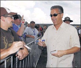 ?? JAMES CRISP/ASSOCIATED PRESS ?? Kentucky men's basketball coach John Calipari (right) signs autographs for fans before the NASCAR Sprint Cup auto race at Kentucky Speedway at Sparta, Ky. Calipari served as honorary pace car driver but his time behind the wheel was cut short by rain.