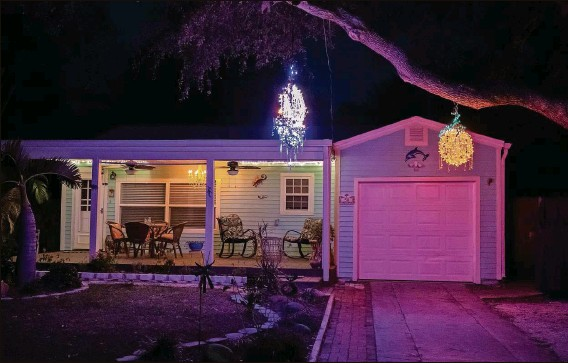 """?? LUIS SANTANA   Times ?? Yard chandeliers glow outside a home in Dunedin. """"It's starting to spread,"""" Dunedin resident Lee Miller says of the chandeliers popping up in more places around the city."""