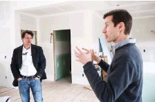 ?? STAFF PHOTO ?? Wayne Williams, left, listens as Michael Walton talks about green|spaces' first NextGen home on the North Shore in 2017. A handful of homes were built on Hamilton Avenue with solar panels and energy efficient designs to reduce net energy consumptio­n to near zero.