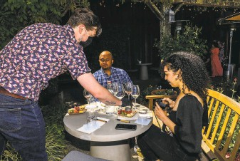 ?? Photos by Yalonda M. James / The Chronicle ?? Julien Tremblay of Lambert Bridge Winery in Healdsburg serves Ryan Robinson (center) and wine influencer Amber Lucas, who documents the moment on Instagram.