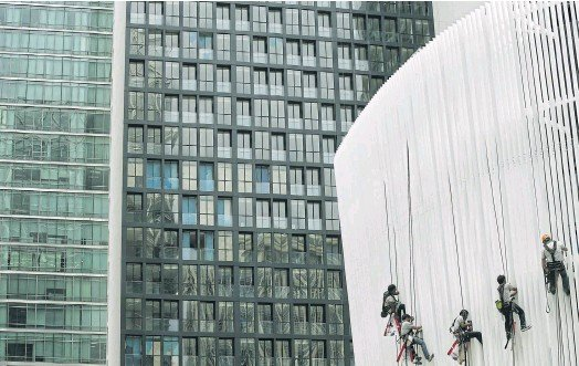 ??  ?? STEADY SUPPLY: Workers install portions of the exterior of a new condominium building in Bangkok. The number of condos newly launched in the capital totalled around 56,000 units in 2017.