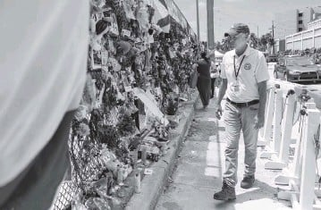 ?? MATIAS J. OCNER mocner@miamiherald.com ?? Surfside Mayor Charles Burkett on Friday visits the Surfside Wall of Hope & Memorial for victims of the Champlain Towers South collapse. He said the town has always been tight-knit but the collapse 'bonded it further.'