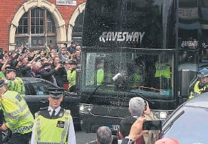 ??  ?? A beer can is hurled at the Manchester United bus as it arrives at the ground