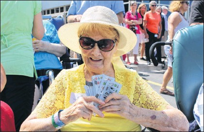 ??  ?? Resident Louise Mullaly tests her luck on the pull-tabs at the Pleasant View Towers garden party on Wednesday.