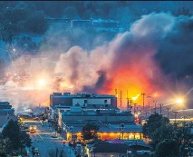 ?? DARIO AYALA/ MONTREAL GAZETTE FILES ?? Smoke and fire rise at night over Lac-Mégantic after a train carrying crude oil derailed and exploded in the town in July 2013.