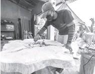 ?? — Gambar Bernama ?? SIAPKAN TEMPAHAN: Pekerja Perabot Eksklusif, Mohd Hafizi Iskandar, 28, sedang menyiapkan salah satu meja kayu yang ditempah pelanggan ketika ditemui Bernama di G Landskap di Jalan Pasir Mas-Rantau Panjang, baru-baru ini.