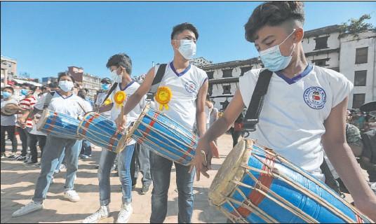 ?? Niranjan Shrestha The Associated Press ?? Devotees play traditional drums during the annual Indra Jatra festival on Sunday in Kathmandu, Nepal.