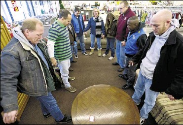 ?? Elizabeth Conley / The Detroit News ?? Employees at the Goodwill store in Canton Township recently pray together while on site. Many homeless people are returning to nonprofit agencies to get help finding employment in a tight job market.