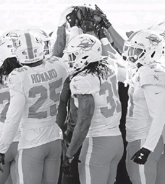 ?? ADAMHUNGER| AP ?? Dolphins free safetyKavo­n Frazier (35) huddles up with teammates before a gameagains­t the NewYorkJet­s onNov. 29 in EastRuther­ford, N.J.