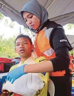 ??  ?? PEGAWAI perubatan merawat peserta yang cedera ketika perlumbaan.
