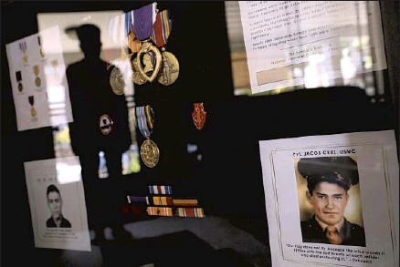 ?? Photographs by Genaro Molina Los Angeles Times ?? RUTHIE SOTO is ref lected in a framed memorial to her uncle, Marine Corps Pvt. Jacob Cruz, that contains his photos and medals, including the Purple Heart. Cruz, an 18-year-old from Boyle Heights, was killed in the 1943 Battle of Tarawa during World War II.