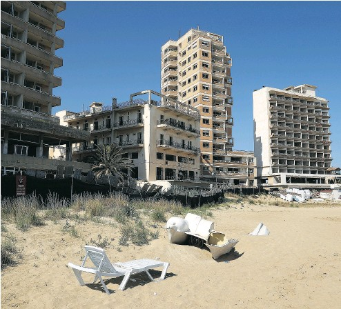 ?? SEAN GALLUP / GETTY IMAGES ?? A public beach in the Turkish Republic of North Cyprus ( TRNC) next to former, decaying hotel buildings that stand inside the Forbidden Zone of Varosha, the setting for The Nightingale Won't Let You Sleep.