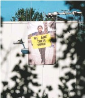 """?? ANIMAL SAVE MOVEMENT ?? A banner was hung on a slaughterhouse wall in Berlin by animal rights activists paying tribute to Russell, who is pictured on the banner holding a sign that reads """"We Are Their Voice."""""""
