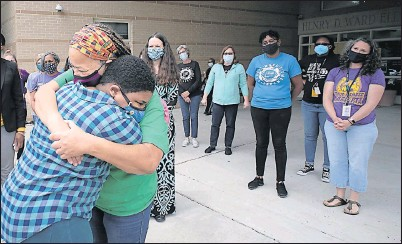 ?? BOB BROWN/TIMES-DISPATCH ?? Kayla Johnson-Brakett, 11 (left), hugs Sherrie Chase, family advocate at Henry D. Ward Elementary School in Henrico County, as she arrives for a surprise visit to drop off presents for 16 teachers who helped her after she was diagnosed with cancer in the fall.