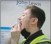 ??  ?? VITAL JOB: A John Lewis worker tests himself