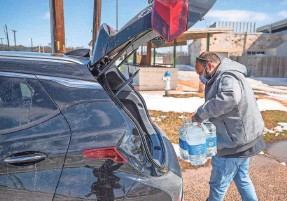 ?? RICARDO B. BRAZZIELL/USA TODAY NETWORK ?? Martin Lopez loads his car with water after refilling the bottles at Georgetown Community Center in Texas on Feb.19.