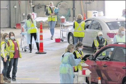 ?? THE ASSOCIATED PRESS ?? Healthworkers process people at a drive- thru flu clinic in Carlton, Minn. The facility offered away to social distance in the coronavirus pandemic, but also served as a test run for the COVID-19 vaccines that health officials are only nowlearning about.