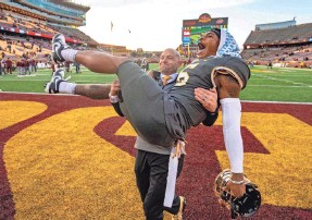 ?? JESSE JOHNSON/USA TODAY SPORTS ?? Minnesota coach P.J. Fleck carries receiver Tyler Johnson off the field after the win over Maryland pushed the Gophers to 8-0.