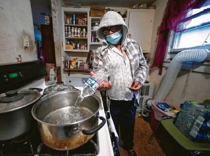 ?? Photos by Brett Coomer / Staff photographer ?? Blinda Whaley pours water into a pan to boil after receiving a case of it and some food from a volunteer group led by Marcel McClinton on Thursday in the 1900 block of Benson Street in Houston.