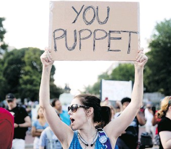 """?? ANDREW HARNIK / THE ASSOCIATED PRESS ?? A woman holds a sign that reads """"You Puppet"""" during a demonstration outside the White House to protest President Donald Trump's meetings in Helsinki with Russian President Vladimir Putin."""