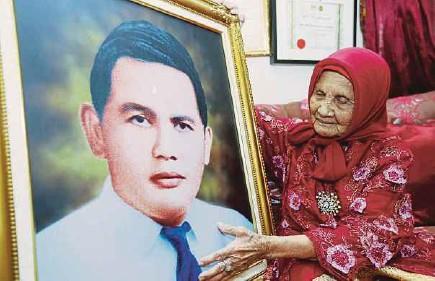 ?? [FOTO DZULKEFFLI MUSTAPHA/BH] ?? Siti Rahmah menunjukkan potret suaminya, Mohd Majzub Yunus.